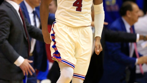 Kansas guard Devonte' Graham (4) celebrates a three-point basket during the overtime of an NCAA college basketball game against West Virginia in Lawrence, Kan., Monday, Feb. 13, 2017. Kansas defeated West Virginia 84-80 in overtime. (AP Photo/Orlin Wagner)