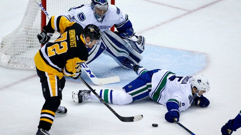 Vancouver Canucks' Luca Sbisa (5) goes to the ice in front of goalie Ryan Miller (30) to block a shot by Pittsburgh Penguins' Patric Hornqvist (72) in the second period of an NHL hockey game in Pittsburgh, Tuesday, Feb. 14, 2017. (AP Photo/Gene J. Puskar)