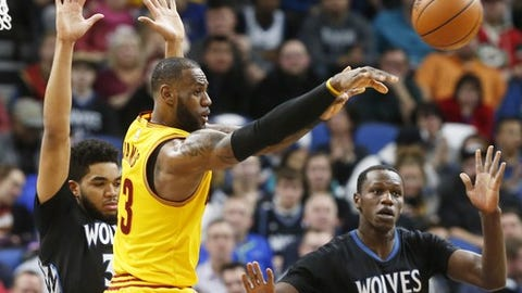 Cleveland Cavaliers' LeBron James gets off a pass as Minnesota Timberwolves' Karl-Anthony Towns, left, and Gorgui Dieng of Senegal defend during the first half of an NBA basketball game, Tuesday, Feb. 14, 2017, in Minneapolis. (AP Photo/Jim Mone)