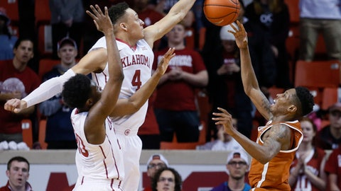 Oklahoma center Jamuni McNeace (4) jumps up in front of teammate Kameron McGusty (20) to block a shot by Texas guard Kerwin Roach Jr., right, during the second half of an NCAA college basketball game in Norman, Okla., Tuesday, Feb. 14, 2017. Oklahoma won 70-66. (AP Photo/Sue Ogrocki)