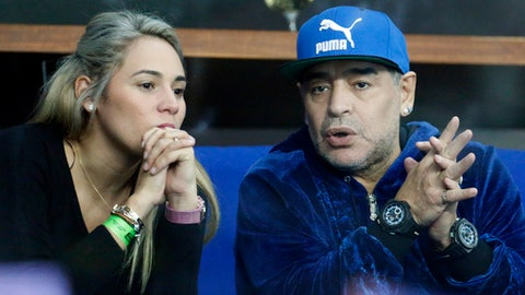 FILE - In this Nov. 25, 2016 file photo, former soccer player Diego Maradona of Argentina sits with his companion Rocio Oliva watching the Davis Cup finals tennis match in Zagreb, Croatia. Police say they were called to investigate an altercation involving Diego Maradona and a woman at a hotel in Madrid. on Wednesday Feb. 15, 2017 after a call from the hotel, but found no evidence of any disturbance after talking to Maradona and the woman. (AP Photo/Darko Bandic, File)