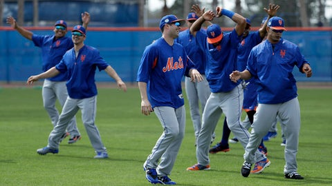 New York Mets second baseman Neil Walker, center, laughs while stretching with teammates during a spring training baseball workout Wednesday, Feb. 15, 2017, in Port St. Lucie, Fla. (AP Photo/David J. Phillip)