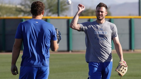 Chicago Cubs' Kris Bryant flips a ball to teammate Anthony Rizzo during a spring training baseball workout Tuesday, Feb. 14, 2017, in Mesa, Ariz. (AP Photo/Morry Gash)