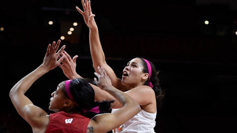 Maryland's Brionna Jones, center shoots over Wisconsin's Avyanna Young, left, during the first half of an NCAA college basketball game, Wednesday, Feb. 15, 2017, in College Park, Md. (AP Photo/Gail Burton)