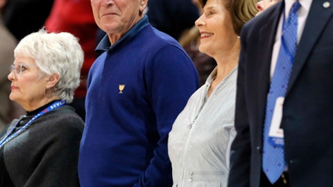 Former President George W. Bush, Laura, center right, and SMU President R. Gerald Turner, right, watch play against Tulane in the second half of an NCAA college basketball game, Wednesday, Feb. 15, 2017, in Dallas. (AP Photo/Tony Gutierrez)