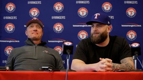 Mike Napoli, right, talks to the media while Texas Rangers manager Jeff Banister looks on during a news conference at spring training baseball practice Thursday, Feb. 16, 2017, in Surprise, Ariz. The Rangers announced that the club has signed free agent Napoli to a one-year contract. (AP Photo/Charlie Riedel)
