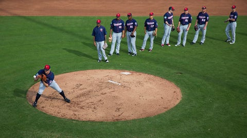 Minnesota Twins pitcher Matt Belisle, left, fields a ball during a drill with fellow pitchers at a baseball spring training workout in Fort Myers, Fla., Thursday, Feb. 16, 2017. (AP Photo/David Goldman)