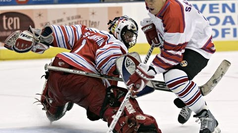 FILE - In this Nov. 6, 2005, file photo, playing for Team Canada, Borje Salming, right, of Sweden, tries to control the puck past Russia's Sergey Kostyukhin during a break in the play for penalty shots in third-period action the 2005 Legends Classic Tour hockey game in Toronto. Though Salming wasn't the first European-born to compete in the NHL when he broke into the league in the 1970s, the former Toronto Maple Leafs defenseman played a key role  in opening the door for the many others to follow him across the Atlantic.  (AP Photo/Adrian Wyld, File)