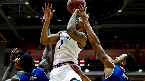 Cincinnati's Jacob Evans (1) shoots against Tulsa's Pat Birt, right, and TK Edogi, left, in the first half of an NCAA college basketball game, Saturday, Feb. 18, 2017, in Cincinnati. (AP Photo/John Minchillo)