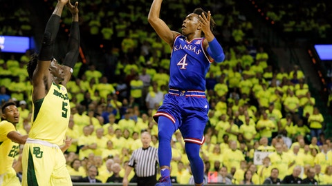 Fans and Baylor are shown wearing day-glow green in a nearly full arena as forward Johnathan Motley (5) defends against a shot by Kansas's Devonte' Graham (4) in the first half of an NCAA college basketball game, Saturday, Feb. 18, 2017, in Waco, Texas. (AP Photo/Tony Gutierrez)