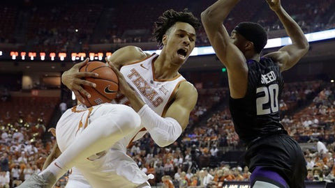 Texas forward Mareik Isom (14) grabs a rebound in front of Kansas State forward Xavier Sneed (20) during the first half of an NCAA college basketball game, Saturday, Feb. 18, 2017, in Austin, Texas. (AP Photo/Eric Gay)