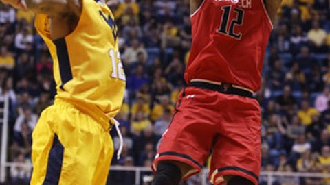 Texas Tech guard Keenan Evans (12) takes a jump shot while being defended by West Virginia guard Tarik Phillip (12) during the first hal of an NCAA college basketball game, Saturday, Feb. 18, 2017, in Morgantown, W.Va. (AP Photo/Raymond Thompson)