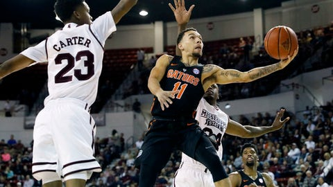 Florida guard Chris Chiozza (11) attempts a layup past Mississippi State guard Tyson Carter (23) in the first half of an NCAA college basketball game in Starkville, Miss., Saturday, Feb. 18, 2017. (AP Photo/Rogelio V. Solis)