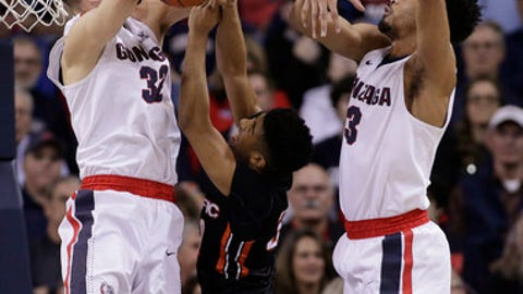 Pacific guard K.J. Smith, center, tries to shoot between Gonzaga forward Zach Collins (32) and forward Johnathan Williams (3) during the first half of an NCAA college basketball game in Spokane, Wash., Saturday, Feb. 18, 2017. (AP Photo/Young Kwak)