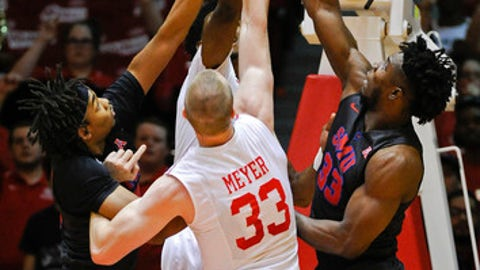 Houston center Kyle Meyer, center, and SMU forwards Semi Ojeleye (33) Ben Moore, left, go up for a rebound during the first half of an NCAA college basketball game, Saturday, Feb. 18, 2017, in Houston. (AP Photo/Eric Christian Smith)
