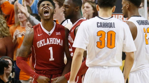 Oklahoma guard Rashard Odomes (1) shouts following a foul by Oklahoma State forward Leyton Hammonds (23) in the first half of an NCAA college basketball game in Stillwater, Okla., Saturday, Feb. 18, 2017. At center are Oklahoma forward Khadeem Lattin and Oklahoma State guard Jeffrey Carroll (30). (AP Photo/Sue Ogrocki)
