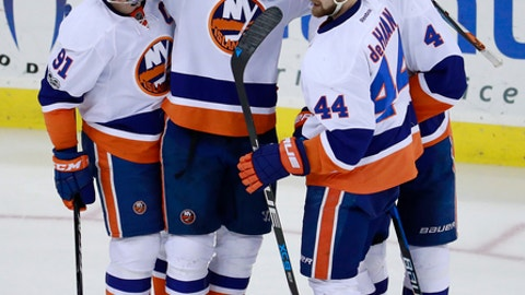 New York Islanders players, from left, John Tavares, Andrew Ladd, Dennis Seidenberg, of Germany, and Calvin de Haan celebrate a goal by Ladd on the New Jersey Devils during the third period of an NHL hockey game, Saturday, Feb. 18, 2017, in Newark, N.J. (AP Photo/Julio Cortez)