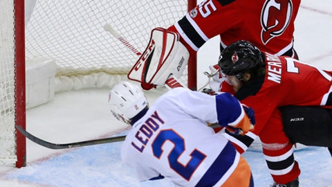 New York Islanders defenseman Nick Leddy (2) misses a chance to score on New Jersey Devils goalie Cory Schneider (35) during the third period of an NHL hockey game, Saturday, Feb. 18, 2017, in Newark, N.J. The Devils won 3-2. Devils' Jon Merrill (7) tries to block the shot during the play. (AP Photo/Julio Cortez)