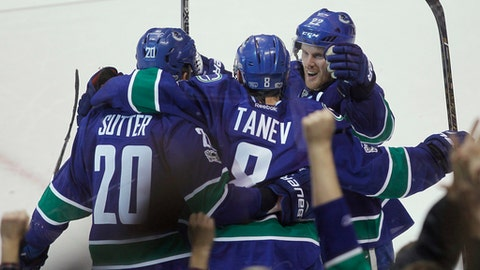 Vancouver Canucks defenseman Christopher Tanev (8) celebrates his game-winning goal against the Calgary Flames with center Brandon Sutter (20) and left wing Daniel Sedin (22)  during overtime of an NHL hockey game Saturday, Feb. 18, 2017, in Vancouver, British Columbia. (Ben Nelms/The Canadian Press via AP)