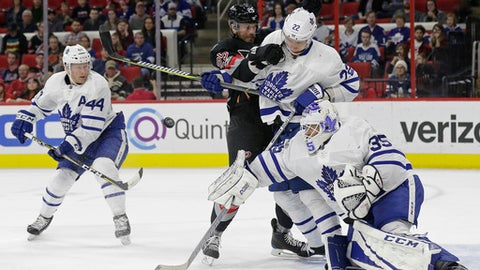 Carolina Hurricanes' Viktor Stalberg (25), of Sweden, tries to score as Toronto Maple Leafs goalie Curtis McElhinney (35), Morgan Rielly (44) and Nikita Zaitsev (22), of Russia, defend during the second period of an NHL hockey game in Raleigh, N.C., Sunday, Feb. 19, 2017. (AP Photo/Gerry Broome)