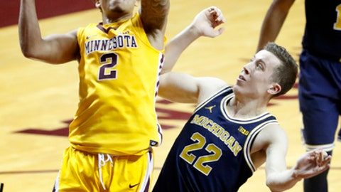 Minnesota's Nate Mason (2) shoots while being defended by Michigan's Duncan Robinson (22) in the first half of an NCAA college basketball game Sunday, Feb. 19, 2017, Minneapolis. (Carlos Gonzalez/Star Tribune via AP)