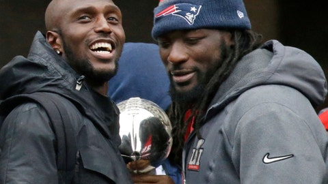 FILE - In this Feb. 7, 2017, file photo, New England Patriots safety Devin McCourty, left, and running back LeGarrette Blount hold a Super Bowl trophy during a rally in Boston to celebrate their win over the Atlanta Falcons in the NFL Super Bowl 51 football game in Houston. McCourty and Blount are among a half-dozen players that have turned down an expected invitation to the White House. (AP Photo/Elise Amendola, File)