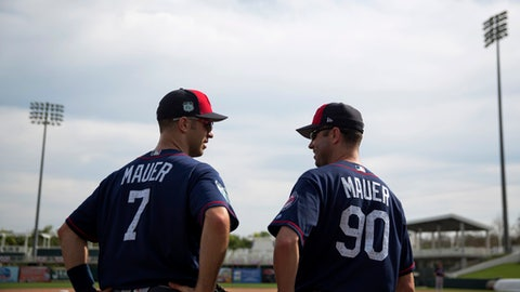 Minnesota Twins first baseman Joe Mauer, left, talks with his brother Jake Mauer, manager of the Twins' minor league team, the Chattanooga Lookouts, as he helps out coaching at major league spring training baseball in Fort Myers, Fla., Tuesday, Feb. 21, 2017. (AP Photo/David Goldman)