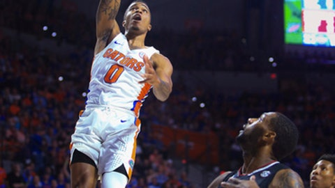 Florida guard Kasey Hill (0) dunks over South Carolina guard Sindarius Thornwell (0) during the first half of an NCAA college basketball game Tuesday, Feb. 21, 2017, in Gainesville, Fla. (AP Photo/Matt Stamey)