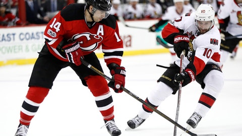 New Jersey Devils center Adam Henrique (14) skates with the puck against Ottawa Senators left wing Tom Pyatt (10) during the second period of an NHL hockey game, Tuesday, Feb. 21, 2017, in Newark, N.J. (AP Photo/Julio Cortez)