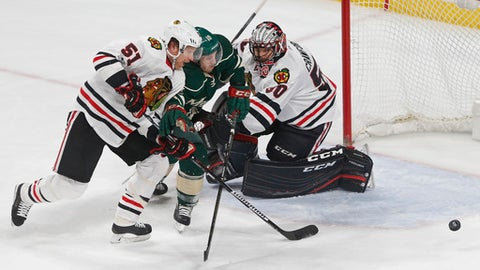 Minnesota Wild's Jordan Schroeder, center, races between Chicago Blackhawks' Brian Campbell, left, and goalie Corey Crawford for the puck during the first period of an NHL hockey game, Tuesday, Feb. 21, 2017, in St. Paul, Minn. (AP Photo/Jim Mone)