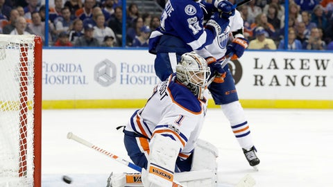 Edmonton Oilers goalie Laurent Brossoit (1) makes a save on a shot by the Tampa Bay Lightning during the second period of an NHL hockey game Tuesday, Feb. 21, 2017, in Tampa, Fla. Lightning's Cedric Paquette (13) looks for a rebound. (AP Photo/Chris O'Meara)