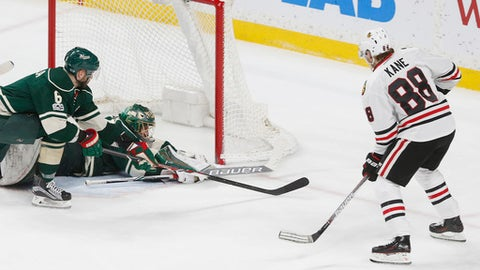 Minnesota Wild goalie Devan Dubnyk, second from left, smothers a shot by Chicago Blackhawks' Patrick Kane, right, during the second period of an NHL hockey game, Tuesday, Feb. 21, 2017, in St. Paul, Minn. (AP Photo/Jim Mone)