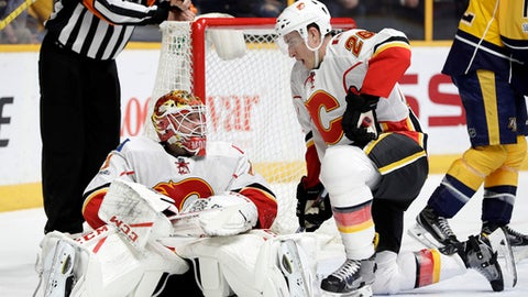 Calgary Flames goalie Brian Elliott (1) and right wing Michael Stone (26) get up off the ice after stopping the puck during the second period of the team's NHL hockey game against the Nashville Predators on Tuesday, Feb. 21, 2017, in Nashville, Tenn. (AP Photo/Mark Humphrey)