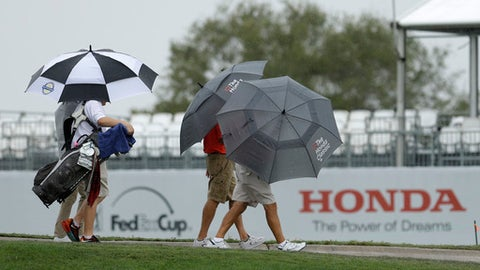 Fans leave the golf course as rain begins at the Honda Classic golf tournament practice, Wednesday, Feb. 22, 2017, in Palm Beach Gardens, Fla. The practice was suspended. (AP Photo/Alan Diaz)
