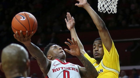 Rutgers guard Nigel Johnson (0) shoots as Michigan guard Muhammad-Ali Abdur-Rahkman (12) tries to block his path during the first half of an NCAA college basketball game Wednesday, Feb. 22, 2017, in Piscataway, N.J. (AP Photo/Mel Evans)