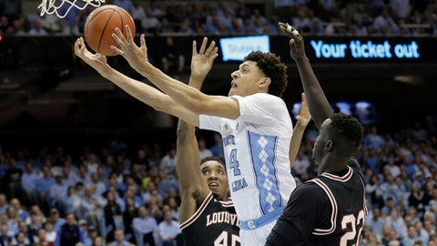 North Carolina's Justin Jackson (44) drives between Louisville's Donovan Mitchell (45) and Deng Adel (22) during the first half of an NCAA college basketball game in Chapel Hill, N.C., Wednesday, Feb. 22, 2017. (AP Photo/Gerry Broome)