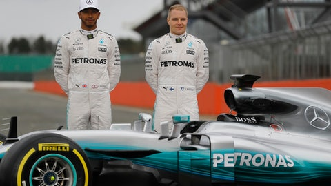 Mercedes drivers Valtteri Bottas of Finland, right, and Lewis Hamilton of Britain pose behind the car during the launch of the new Mercedes F1 car at the Silverstone racetrack in Towcester, England, Thursday, Feb. 23, 2017. (AP Photo/Frank Augstein)