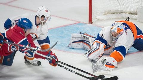New York Islanders goaltender Thomas Greiss makes a save against Montreal Canadiens' Artturi Lehkonen, left, as Islanders' Alan Quine defends during the second period of an NHL hockey game Thursday, Feb. 23, 2017, in Montreal. (Graham Hughes/The Canadian Press via AP)