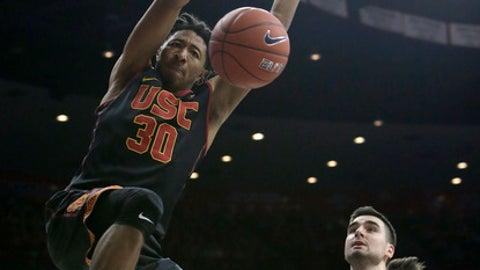 Southern California guard Elijah Stewart (30) dunks over Arizona center Dusan Ristic during the first half of an NCAA college basketball game, Thursday, Feb. 23, 2017, in Tucson, Ariz. (AP Photo/Rick Scuteri)