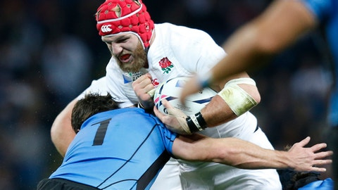 FILE - In this Saturday, Oct. 10, 2015 file photo, Uruguay's Mateo Sanguinetti tackles England's James Haskell during their Rugby World Cup Pool A match at Manchester City Stadium, Manchester, England. Coach Eddie Jones resisted the temptation for wholesale reform by limiting England's changes to four for the Six Nations match against last-placed Italy on Sunday, Feb. 26, 2017 at Twickenham. He has given first starts of the year for openside flanker James Haskell, scrumhalf Danny Care, and centre Ben Te'o. (AP Photo/Jon Super, file)
