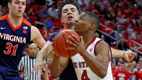 Virginia's London Perrantes, center, defends North Carolina State 's Dennis Smith Jr., right,  with Jarred Reuter, left, nearby during the first half of an NCAA college basketball game in Raleigh, N.C., Saturday, Feb. 25, 2017. (AP Photo/Karl B DeBlaker)