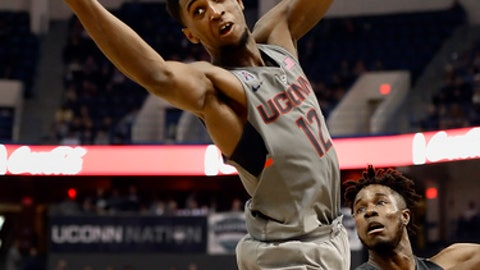 Connecticut's Kentan Facey reaches to catch a pass as SMU's Semi Ojeleye, right, defends in the second half of an NCAA college basketball game, Saturday, Feb. 25, 2017, in Hartford, Conn. (AP Photo/Jessica Hill)