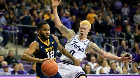 West Virginia guard Tarik Phillip (12) dribbles inside as TCU guard Jaylen Fisher (0) defends in the first half of an NCAA college basketball game, Saturday, Feb. 25, 2017, in Fort Worth, Texas. (AP Photo/Ron Jenkins)