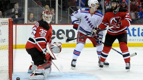 New York Rangers' Chris Kreider, center, celebrates his goal as New Jersey Devils goaltender Cory Schneider, left, eyes the puck coming out of the net and Devils' Kyle Palmieri looks on during the first period of an NHL hockey game Saturday, Feb. 25, 2017, in Newark, N.J. (AP Photo/Bill Kostroun)