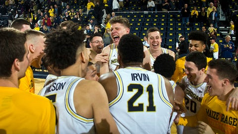 Michigan forward Moritz Wagner, center, celebrate with teammates on the court after an NCAA college basketball game against Purdue in Ann Arbor, Mich., Saturday, Feb. 25, 2017. Michigan won 82-70. (AP Photo/Tony Ding)