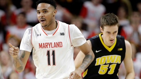Maryland guard Jared Nickens, left, points to a teammate after making a 3-pointer, in front of Iowa forward Nicholas Baer during the first half of an NCAA college basketball game, Saturday, Feb. 25, 2017, in College Park, Md. (AP Photo/Patrick Semansky)