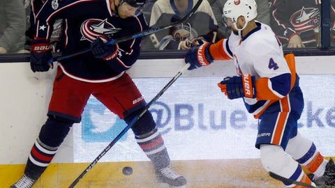 Columbus Blue Jackets defenseman Jack Johnson, left, works for the puck against New York Islanders defenseman Dennis Seidenberg, of Germany, during the third period of an NHL hockey game in Columbus, Ohio, Saturday, Feb. 25, 2017. The Blue Jackets won 7-0. (AP Photo/Paul Vernon)