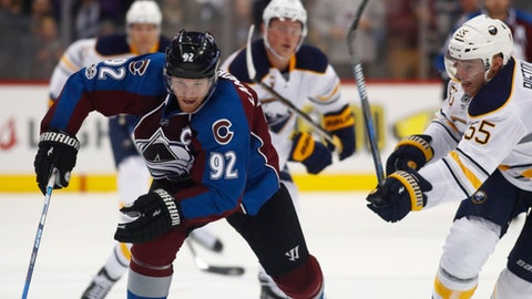 Colorado Avalanche left wing Gabriel Landeskog, left, of Sweden, drives past Buffalo Sabres defenseman Rasmus Ristolainen, of Finland, to score an empty-net goal late in the third period of an NHL hockey game Saturday, Feb. 25, 2017, in Denver. The Avalanche won 5-3. (AP Photo/David Zalubowski)