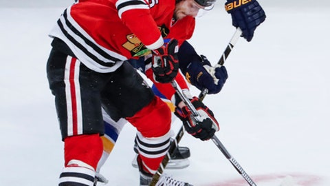 Chicago Blackhawks center Artem Anisimov (15) battles for the puck against St. Louis Blues defenseman Kevin Shattenkirk (22) during the second period of an NHL hockey game Sunday, Feb. 26, 2017, in Chicago. (AP Photo/Kamil Krzaczynski)