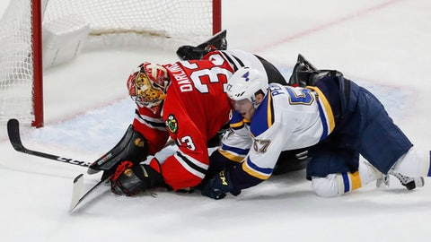 Chicago Blackhawks goalie Scott Darling (33) collides with St. Louis Blues left wing David Perron (57) while battling for the puck during the second period of an NHL hockey game, Sunday, Feb. 26, 2017, in Chicago. (AP Photo/Kamil Krzaczynski)
